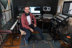 Happy music producer working at a recording studio - arts and entertainment concepts